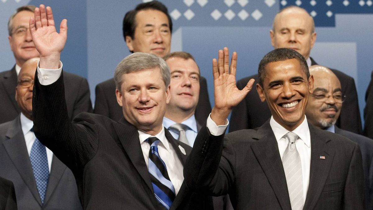 Stephen Harper and Barack Obama wave as members of the summit pose for photo