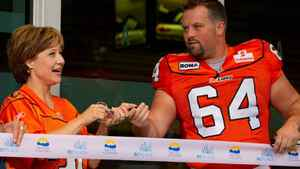 British Columbia Premier Christy Clark, left, and B.C. Lions' Angus Reid take part in a ribbon cutting to officially open the renovated B.C. Place stadium before the Lions played the Edmonton Eskimos in a CFL football game in Vancouver, B.C., on Friday September 30, 2011. The stadium was closed for 18-months to undergo a $563-million renovation which included a new retractable fabric roof. THE CANADIAN PRESS/Darryl Dyck