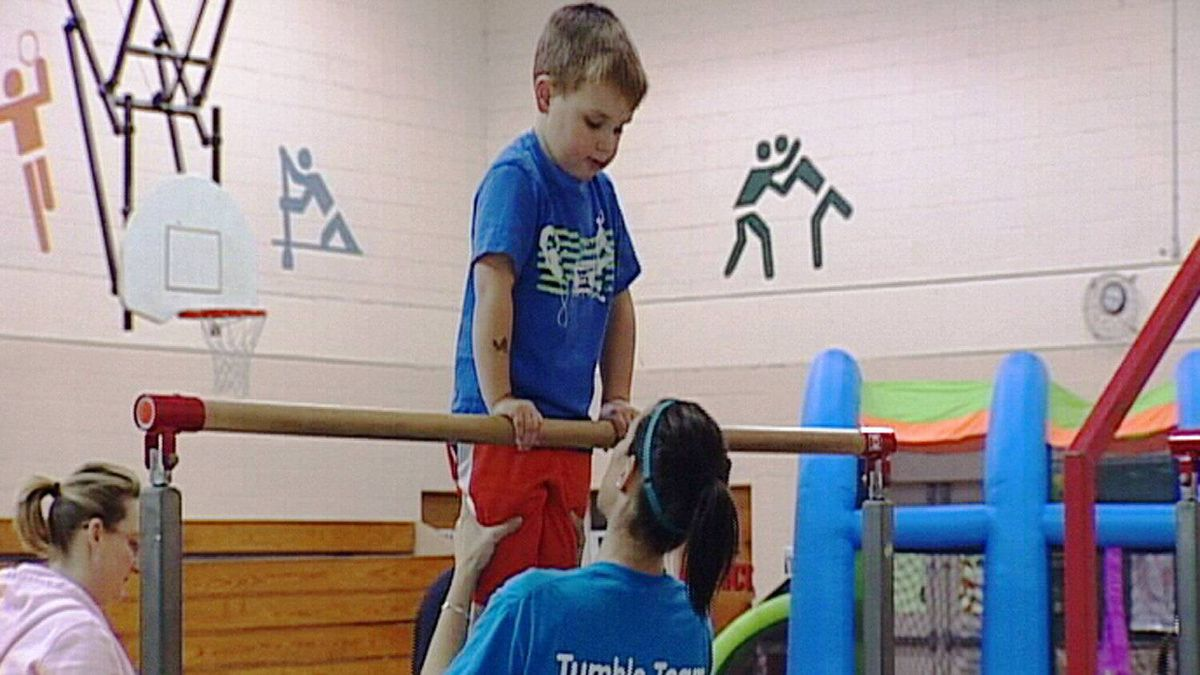 A child performs on a high bar during a Go-Go Gymastics Kinder Kids class.