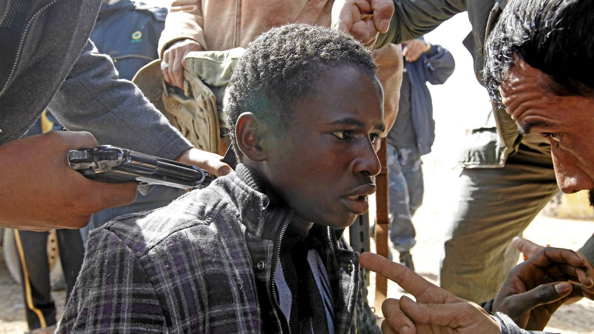 Rebels hold a young man at gunpoint, who they accuse of being a loyalist to Libyan leader Muammar Gaddafi, between the towns of Brega and Ras Lanuf, March 3, 2011