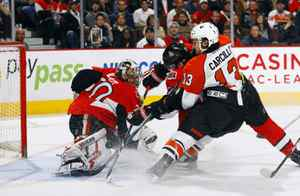 Brian Elliot of the Ottawa Senators makes a pad save while teammate Anton Volchenkov battles with Dan Carcillo of the Philadelphia Flyers for the loose puck in a game at Scotiabank Place on March 23, 2010 in Ottawa, Canada. The Ottawa Senators lead the Philadelphia Flyers 1-0 after one period.
