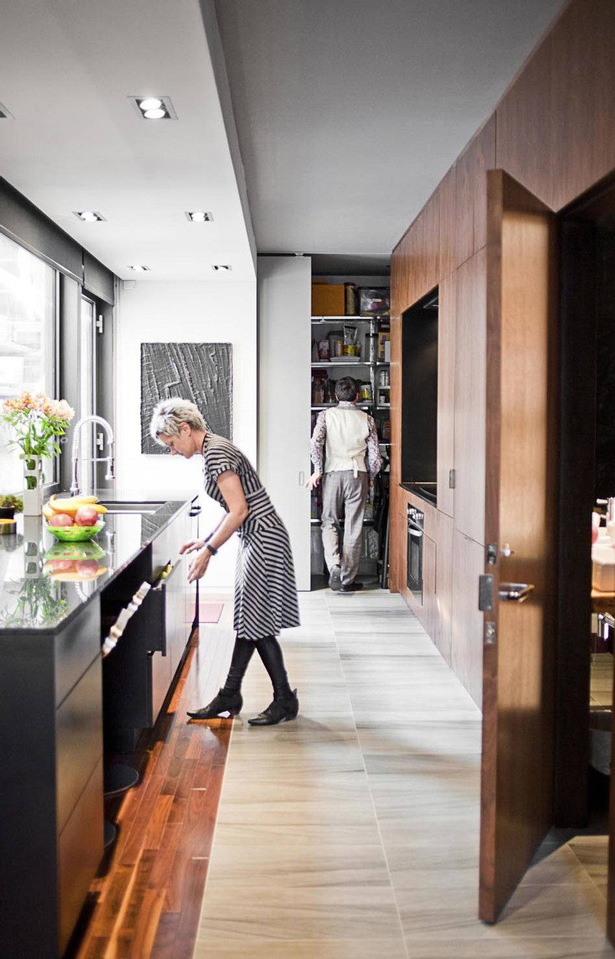 A walk-in pantry is tucked behind floor-to-ceiling sliding doors. They left room under the stairs for an off-the-kitchen bathroom.