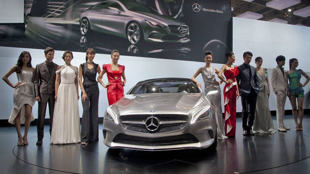 Models pose next to a Mercedes Benz concept style coupe.