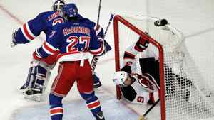 New Jersey Devils' Zach Parise, right, goes into the net after his shot was deflected by New York Rangers goalie Henrik Lundqvist, rear, of Sweden, and Ryan McDonagh (27). (AP Photo/Julio Cortez)