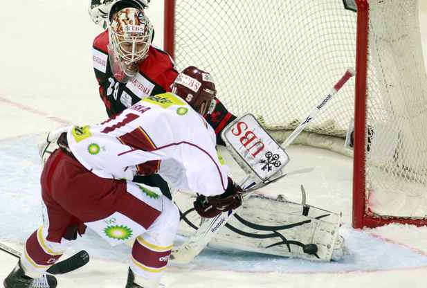 Team Canada's goalkeeper Jeff Deslauriers (L) is challenged by Tomas Kurka of Sparta Prague during their ice hockey match at the Spengler Cup tournament in the Swiss mountain resort of Davos December 29, 2010.
