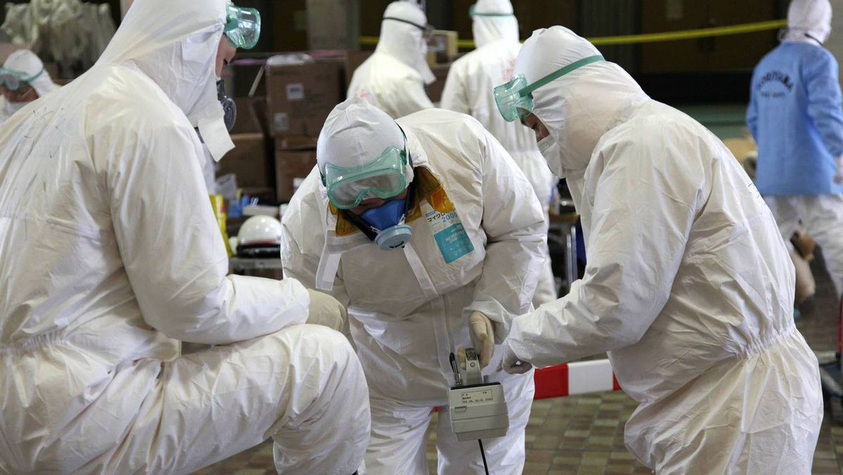Radiation scanning crews check eath other's levels as they change their working shift at a screening centre in Koriyama in Fukushima prefecture, 60km west of TEPCO's striken Fukushima No.1 nuclear power plant, on March 18, 2011.
