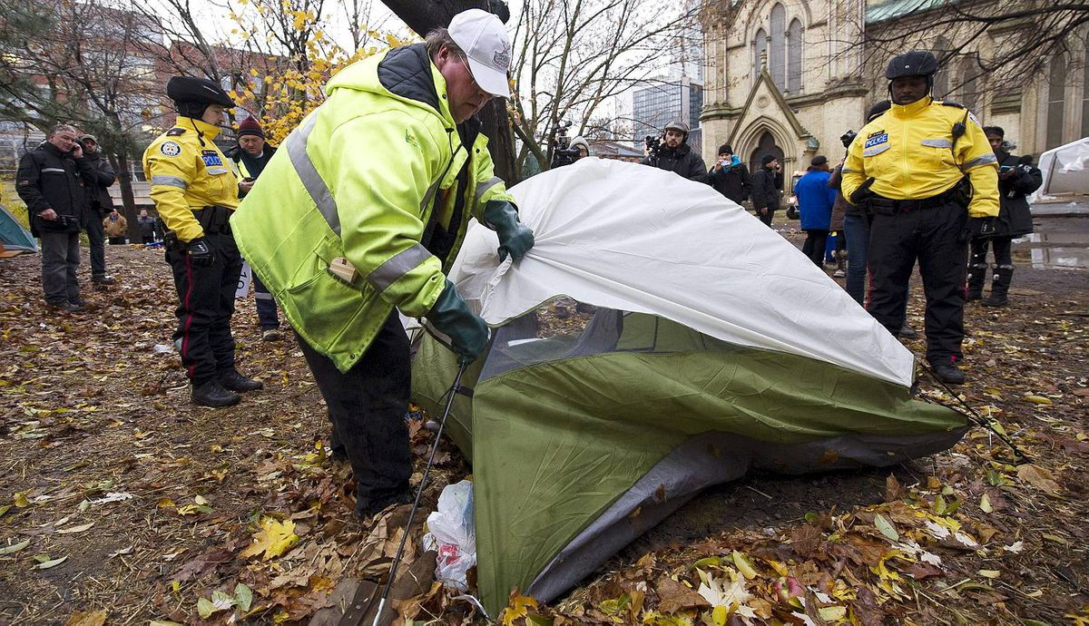 City of Toronto workers clear structures and tents as they are accompanied by Toronto Police at the Occupy Toronto site in St. James Park in Toronto on Wednesday, Nov. 23, 2011. THE CANADIAN PRESS/Nathan Denette
