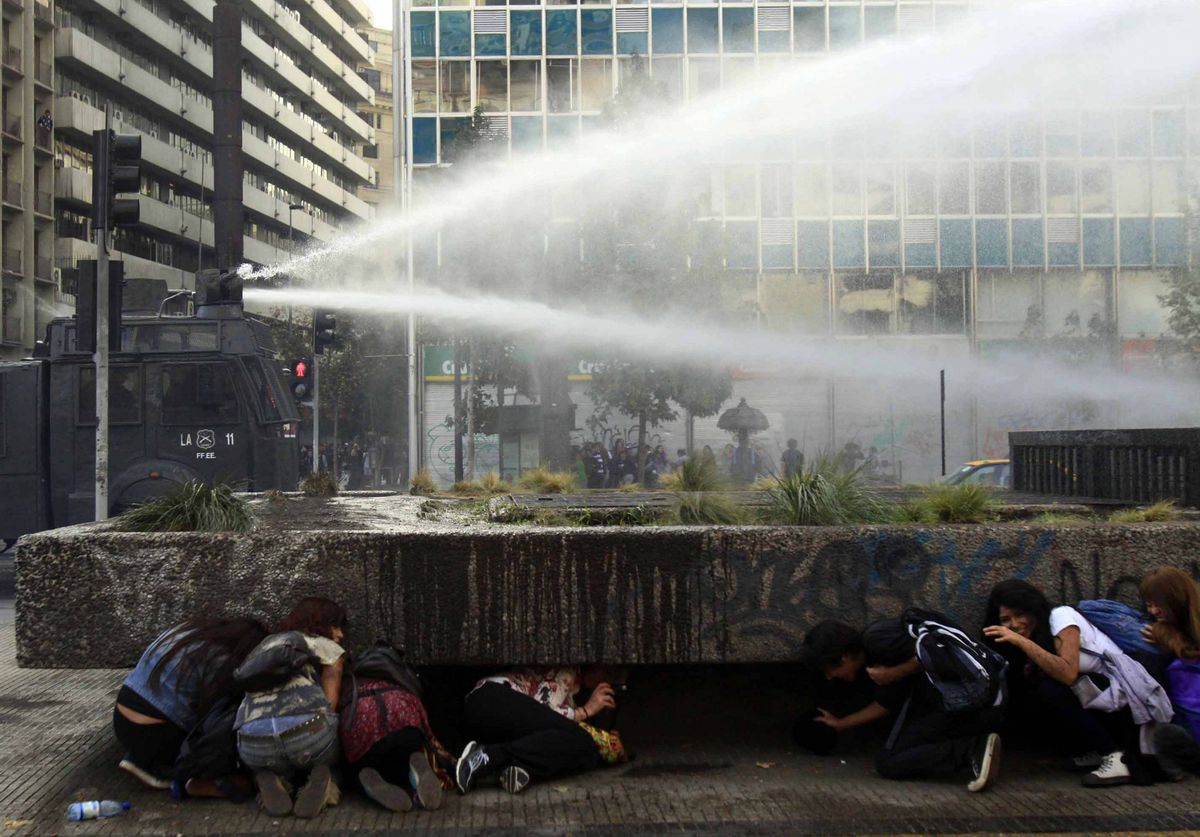 Students take cover from police water canons during a demonstration for education reform in downtown Santiago, Chile.