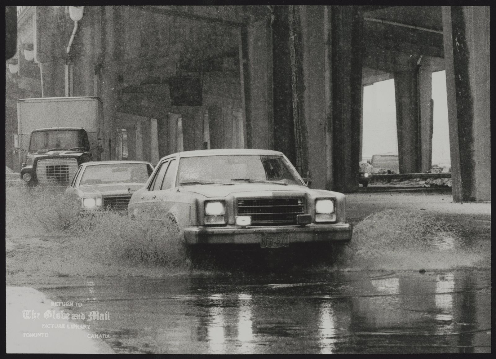 The notes transcribed from the back of this photograph are as follows: A broken water main flooded the area near the intersection of York Street, Front Street and University Avenue and south to Lakeshore Blvd. this morning, causing massive traffic jams for communters.