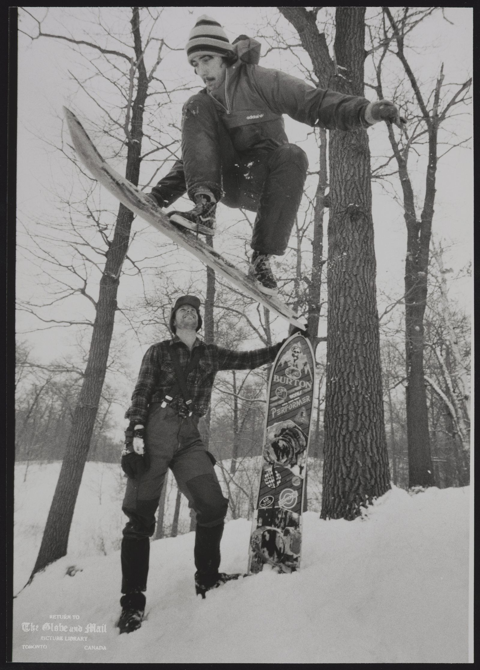 SNOWBOARDS Riding snowboard, Greg Lowe flies high off jump in Toronto's High Park as his friend Peter Wheldrake watches. Both are members of Hogtown Snowboard Team