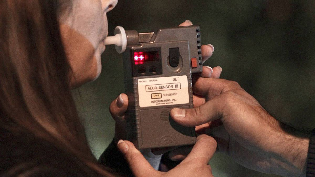An RCMP officer performs a breathalyzer test on a driver during a roadside check in Surrey, B.C.