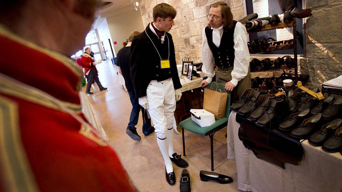 Shoemaker Robert Land, right, of Guelph, Ont., discusses the fit of a new pair of shoes with Alexander Kuehner.