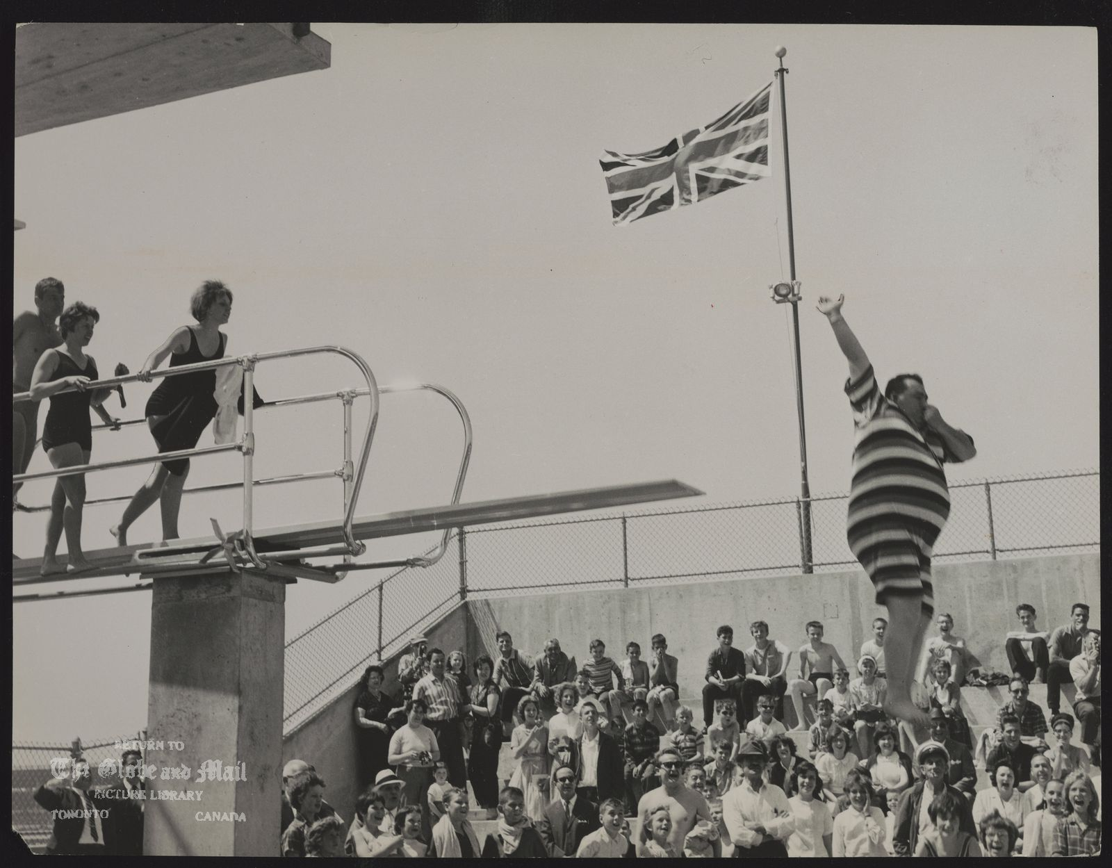 The notes transcribed from the back of this photograph are as follows: JOSEPH PICCININNI Toronto Alderman his glorious girth swathed in georgious stripes, clowns at pool opening at Beaches Pool