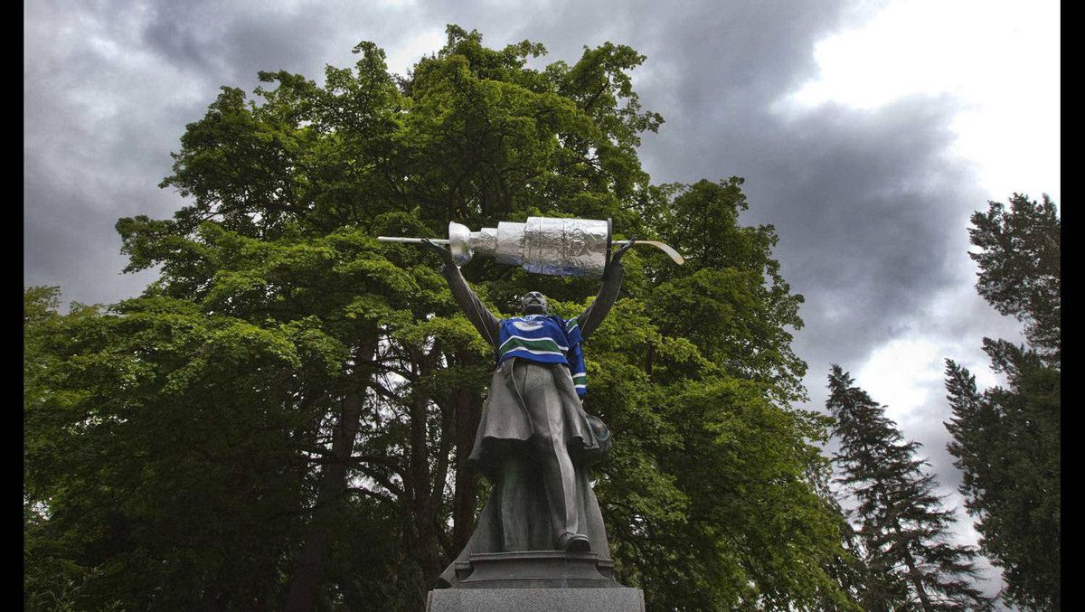 A statue of Lord Stanley is pictured draped in a Vancouver Canucks sweater and with a replica of the NHL's Stanley Cup trophy placed in its hands.