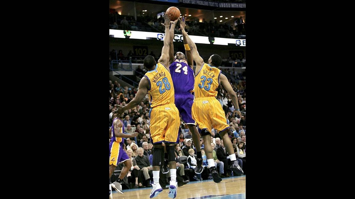 Los Angeles Lakers guard Kobe Bryant (24) pulls up a jump shot over New Orleans Hornets center D.J. Mbenga (28) and guard Willie Green (33) during the first half of their NBA basketball game in New Orleans Feb. 5, 2011.