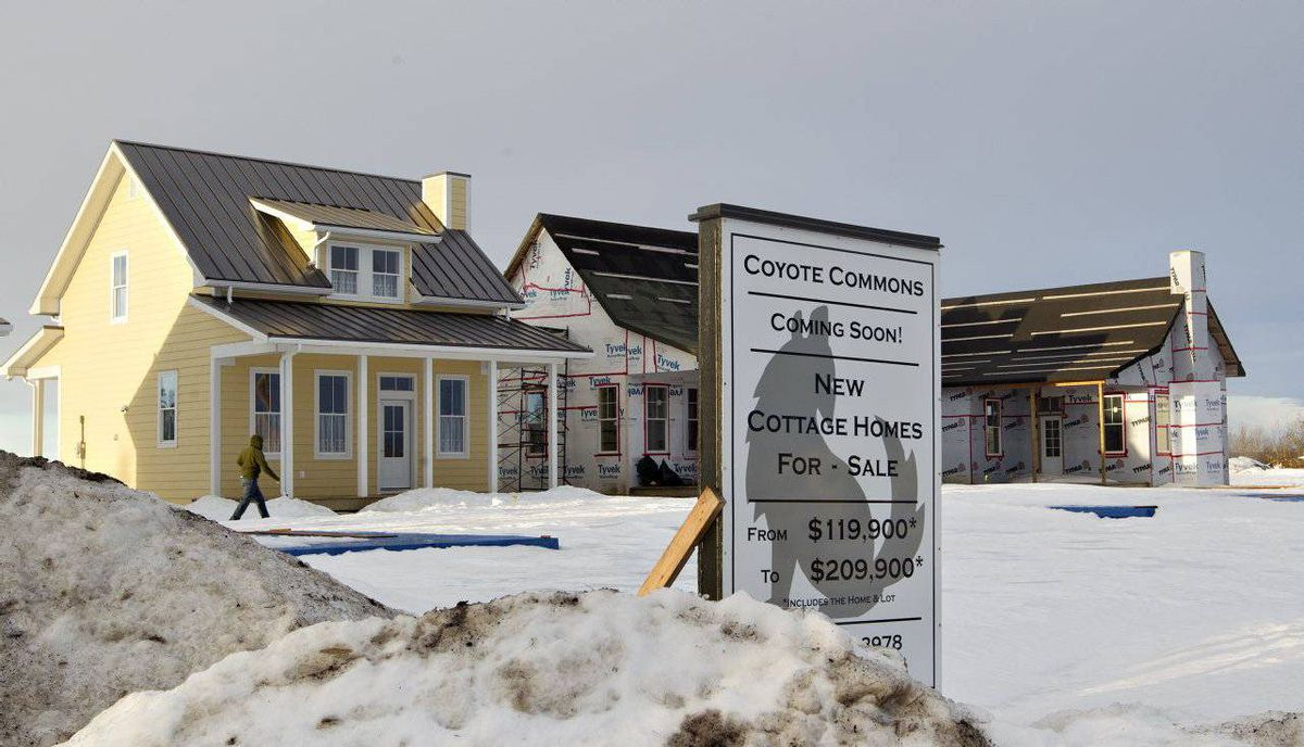 A man walks in by the new cottages being built for resale in the Coyote Commons area of Chipman.