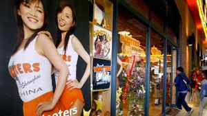 Chinese customers enter the newly opened Hooters restaurant in Shanghai in 2004.