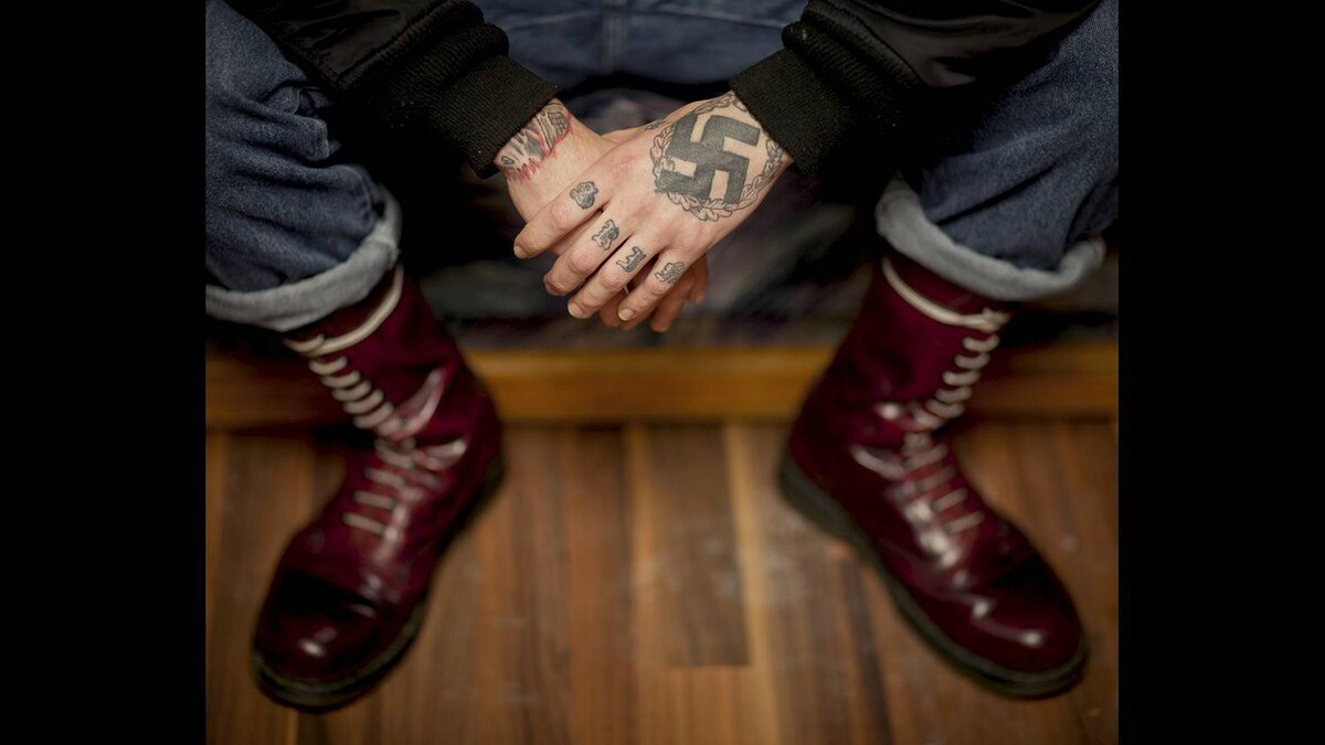 Kyle McKee listens to metal music, shaves his head, and is covered in tattoos. He identifies as a National Socialist. He wears mostly black, except for red Doc Martens.