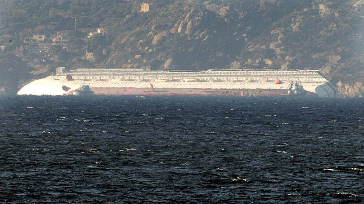 The luxury cruise ship Costa Concordia lies virtually flat, its right-hand side submerged in the water, along the coast of the tiny Tuscan island of Giglio, Italy, Saturday, Jan. 14, 2012. A luxury cruise ship ran aground off the coast of Tuscany, sending water pouring in through a 160-foot (50-meter) gash in the hull and forcing the evacuation of some 4,200 people from the listing vessel early Saturday, the Italian coast guard said.