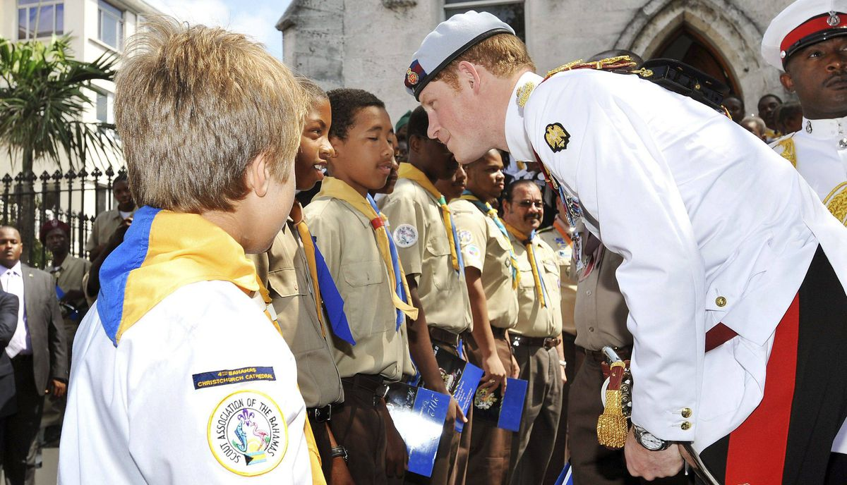 Prince Harry talks to a group of Boy Scouts after attending a church service at Christ Church Cathedral in Nassau on March 4, 2012.