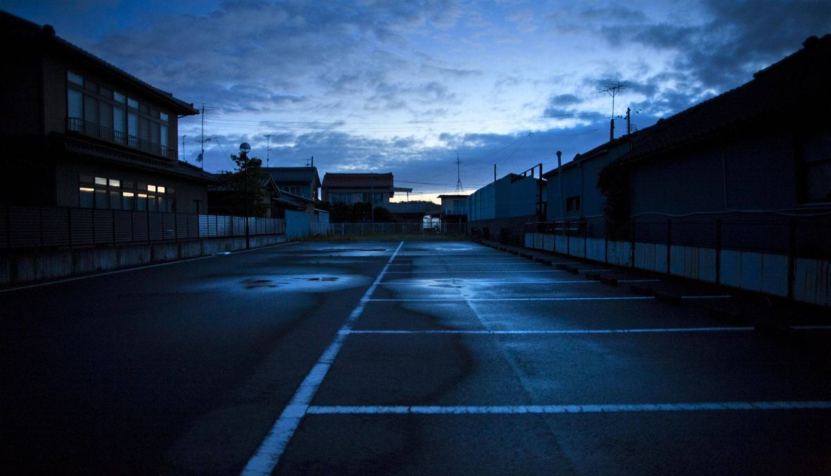 A parkinglot sits empty in the town of Odaka, inside the 20-kilometer exclusion zone around the Fukushima Daiichi nuclear plant July 23, 2011. A year after the Tsunami, cleanup has begun, but experts say areas inside the nuclear exclusion zone will be difficult to decontaminate.