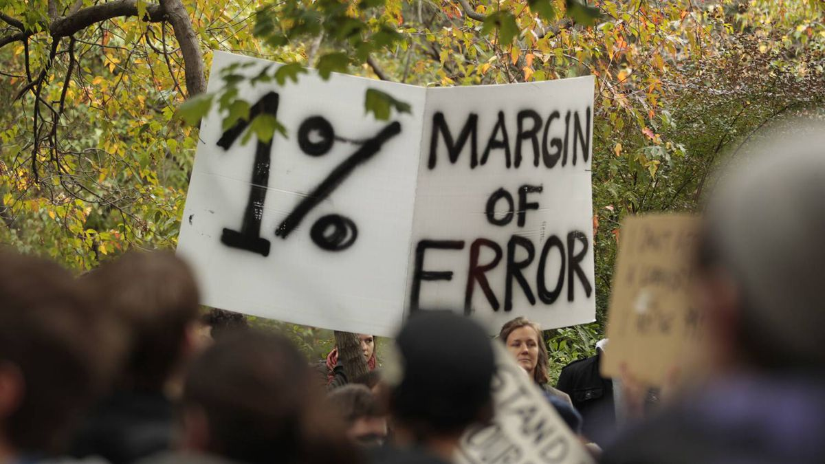 A protester hold a sign showing displeasure at the economic gap between the world's rich and poor at the Occupy Toronto protests on October 15, 2011.