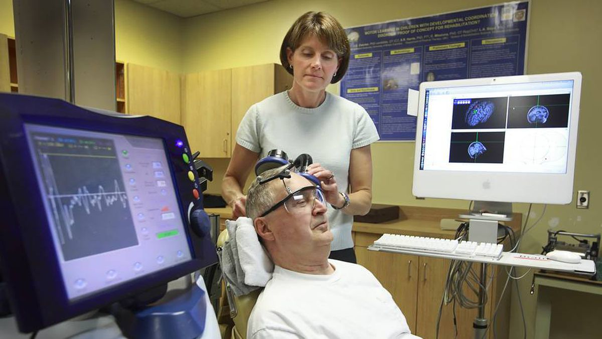 Dr. Lara Boyd, an assistant professor in the Department of Physical Therapy at UBC Hospital in Vancouver, looks on as stroke survivor Ted Wasnick has electromagnetic waves sent into his premotor cortexes, a brain region associated with learning motor skills.