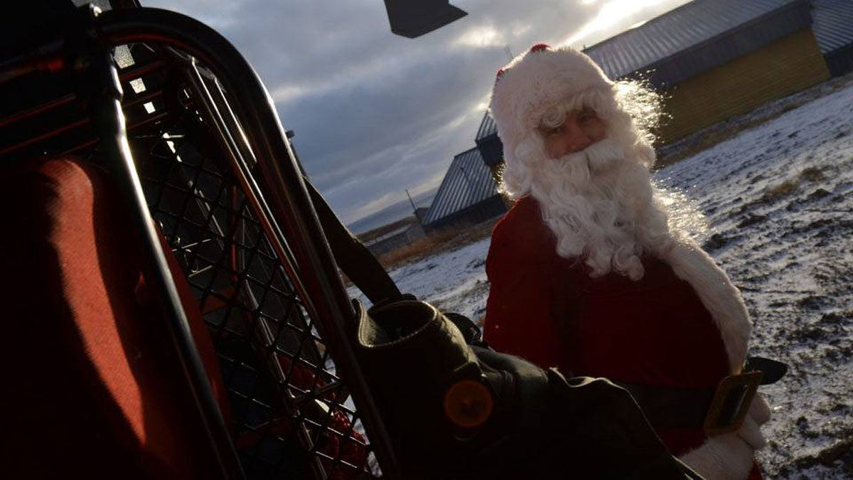 Santa Claus disembarks from a Coast Guard HH-60 helicopter in Akhiok, Alaska.