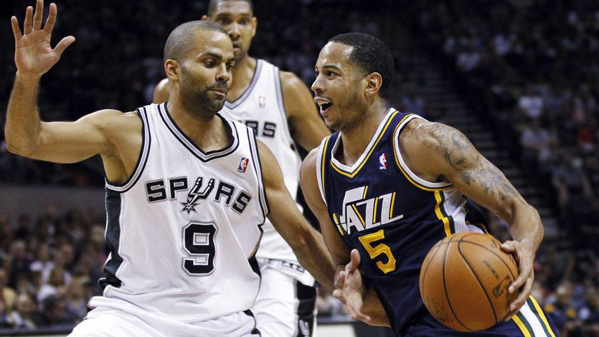 Utah Jazz guard Devin Harris, right, drives on San Antonio Spurs guard Tony Parker as centre Tim Duncan watches during the first half of their Western Conference quarter-final playoff basketball game in San Antonio on Sunday.