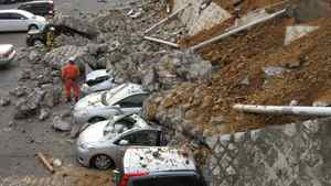 Vehicles crushed by a collapsed wall at a car park in Mito city, Japan.