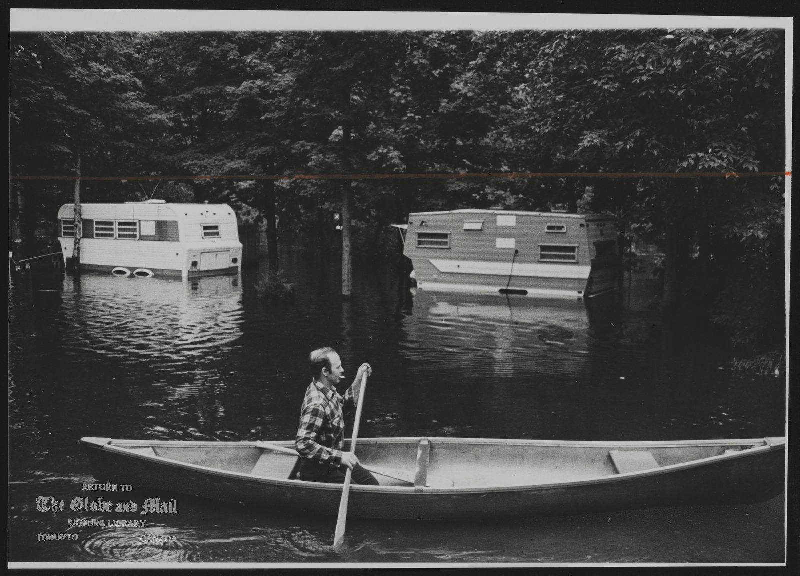 FLOODS Canada Allan McCutcheon canoes through Silver Sand Trailer Park, Huntsville.