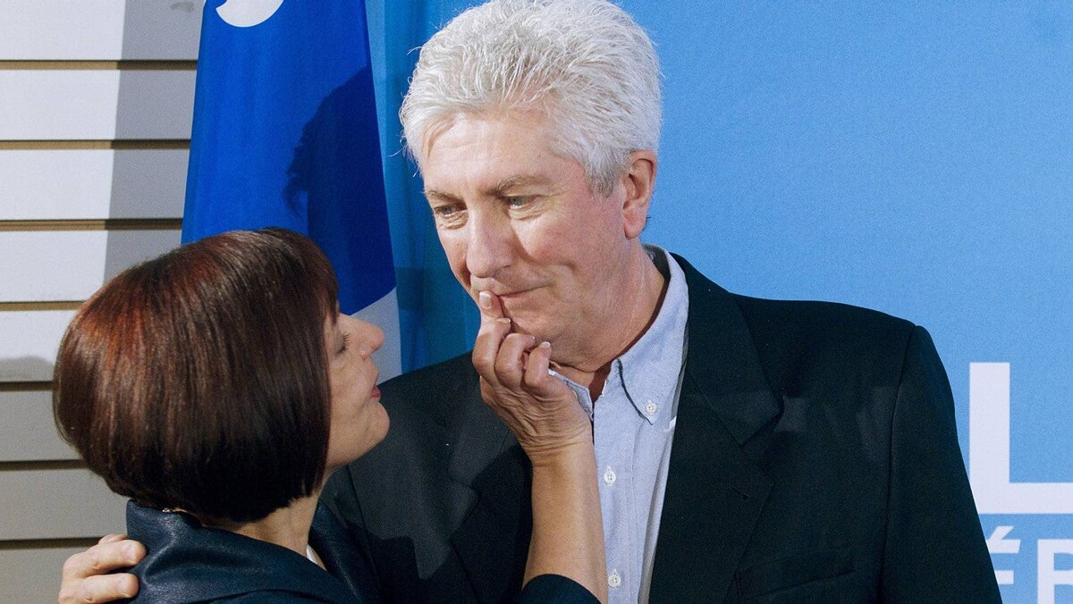 Bloc Quebecois leader Gilles Duceppe has lipstick wiped off his lips following a kiss from his wife Yolande Brunelle (L) during a campaign stop in Montreal, April 10, 2011.