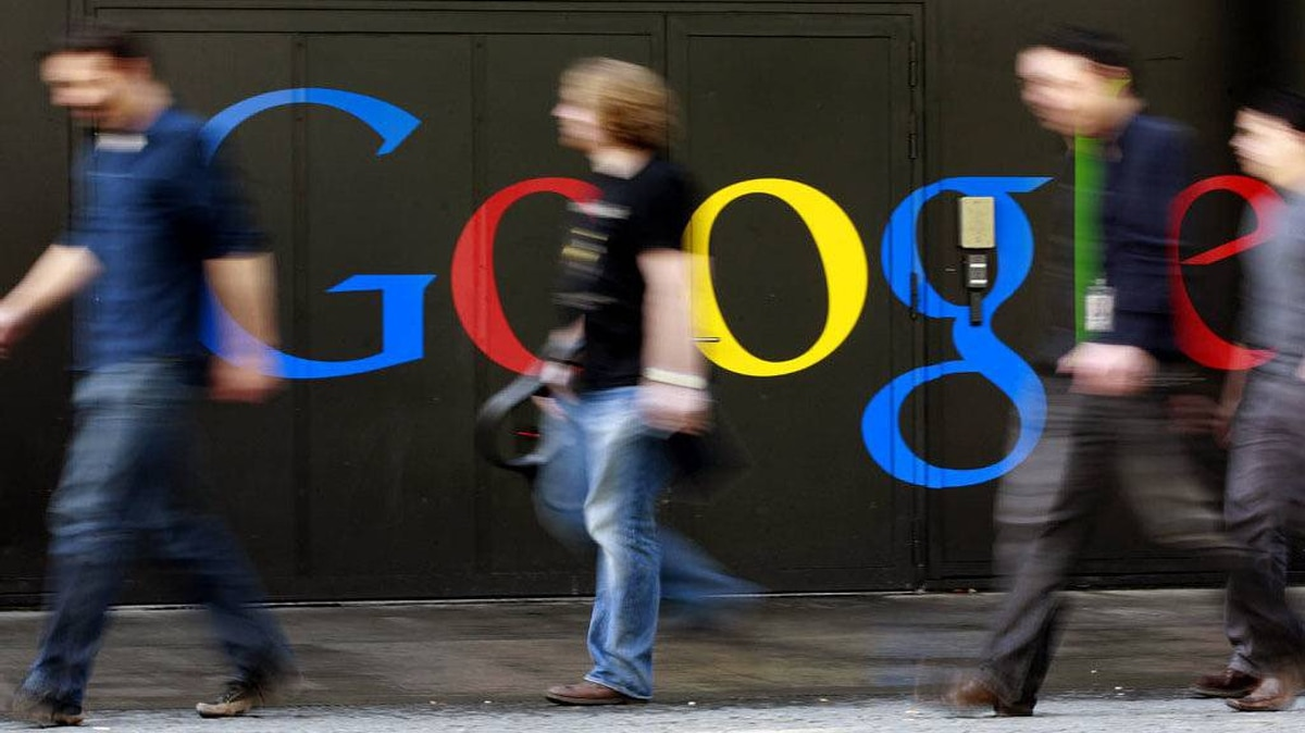 People walk past a logo next to the main entrance of the Google building in Zurich in this March 9, 2011 file photo. Google Inc will launch a mobile payment system on Thursday, in the latest bid to help consumers pay at the checkout with smartphones instead of traditional credit cards, a person familiar with the matter told Reuters on May 24, 2011.