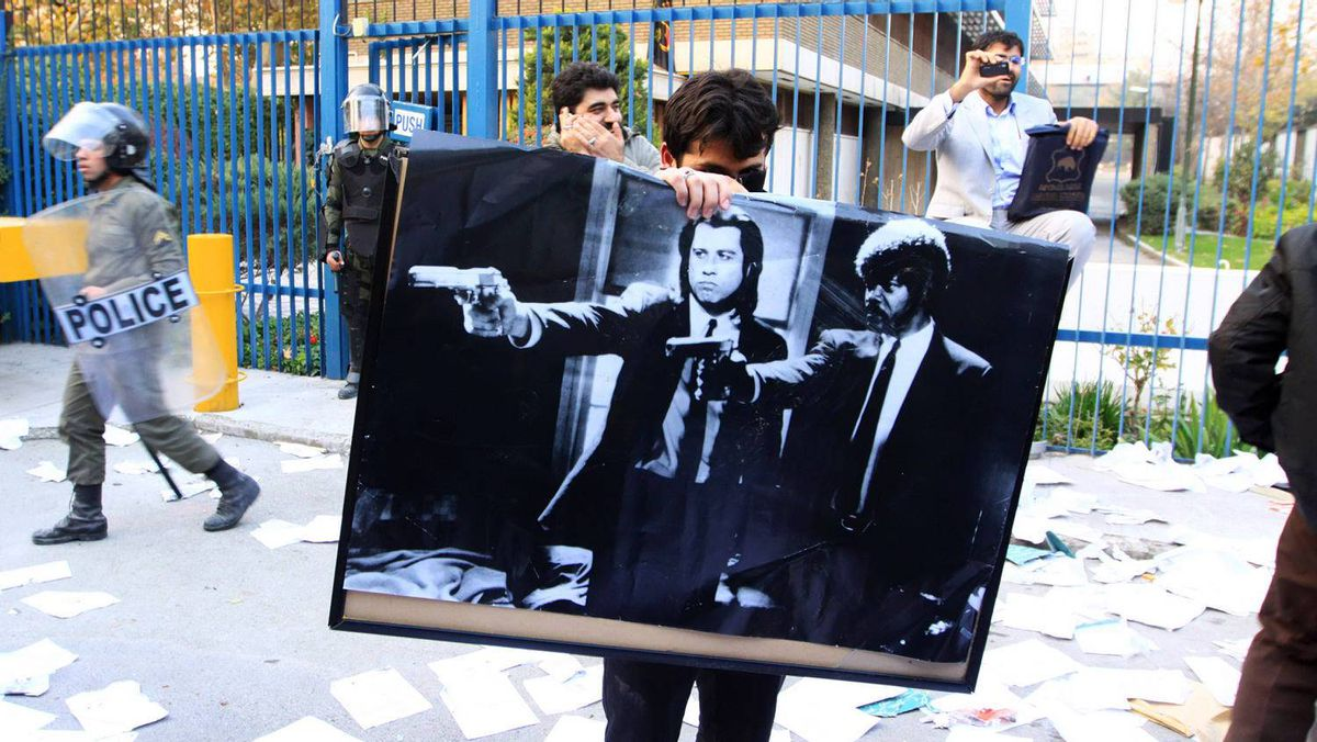 TEHRAN, IRAN - NOVEMBER 29: A man holds a poster featuring American actors John Travolta and Samuel L. Jackson in a scene from the film 'Pulp Fiction' following a break in at the British Embassy during an anti-British demonstration in the Iranian capital on November 29, 2011 in Tehran, Iran. Getty Images