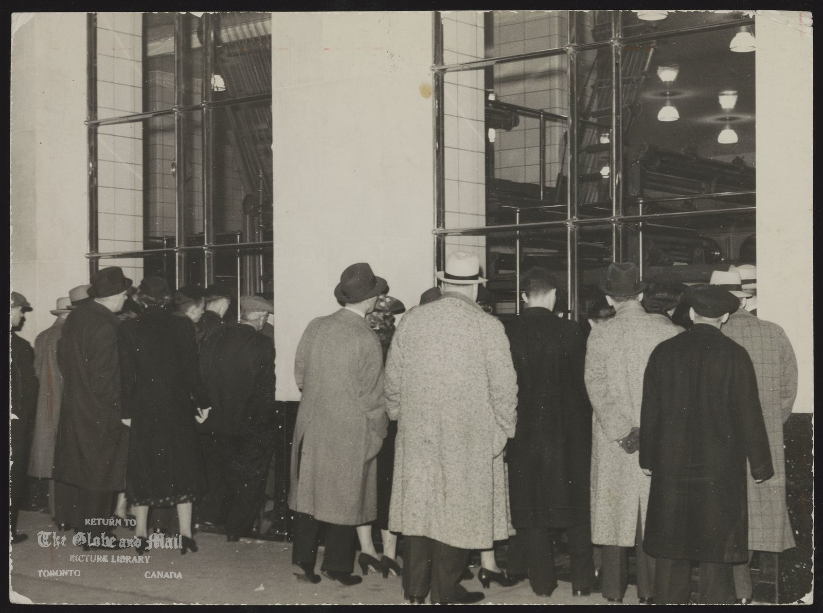 The notes transcribed from the back of this photograph are as follows: TORONTO GLOBE AND MAIL HISTORICAL-MISCELLANEOUS [WILLIAM H. WRIGHT BUILDING OPENS -- People on Yonge Street in Toronto looking through windows at Globe and Mail's new presses in the William H. Wright building, April 25, 1938. Photo by John Boyd / The Globe and Mail. (Scanned from glass plate Negative #51073 / 38115-07). ]