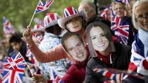 Royal supporters wave flags and wear masks depicting Britain's Prince William and Kate Middleton, along the procession route in London April 29, 2011.