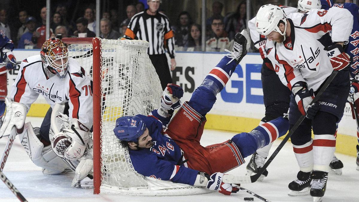 Washington Capitals goalie Braden Holtby (L) watches as New York Rangers' Brian Boyle (C) battles with Washington Capitals' Dennis Wideman (R) during the second period. REUTERS/Ray Stubblebine