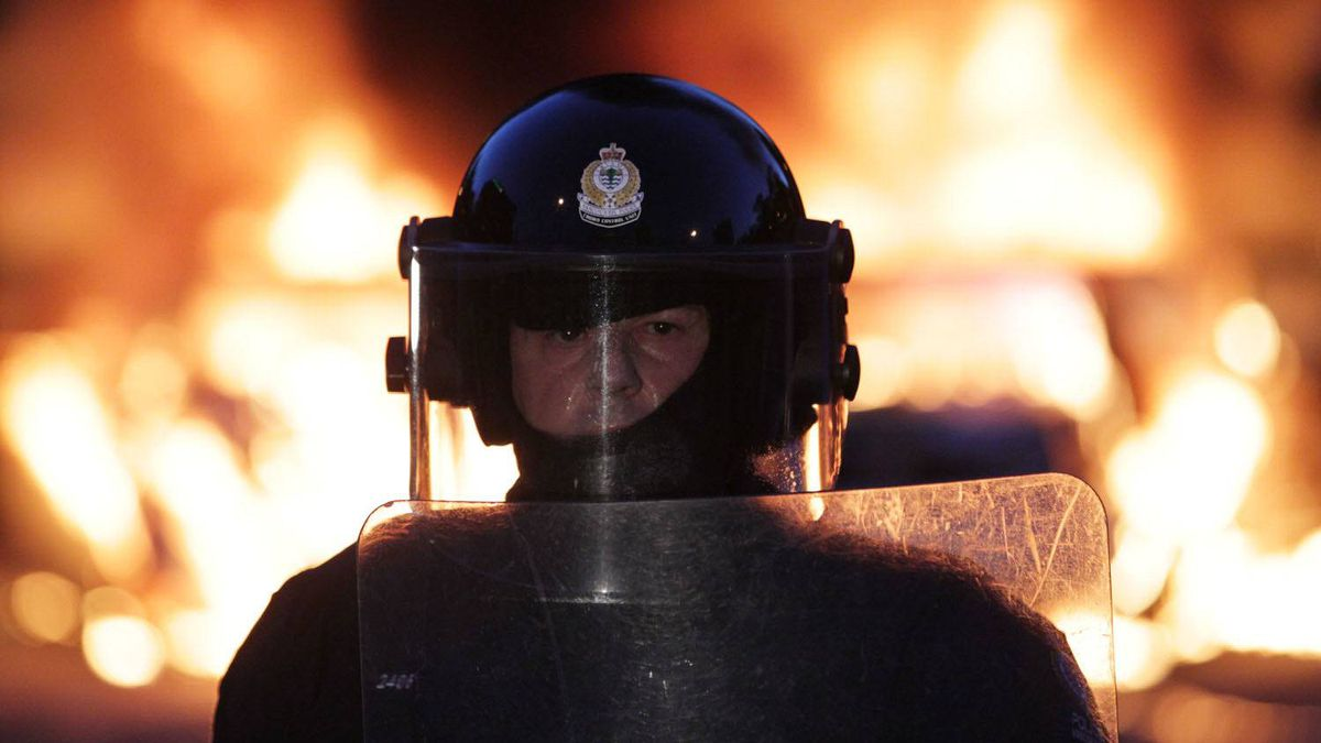 Riot officers keep a perimeter around two burning police cars in downtown Vancouver June 15, 2011.