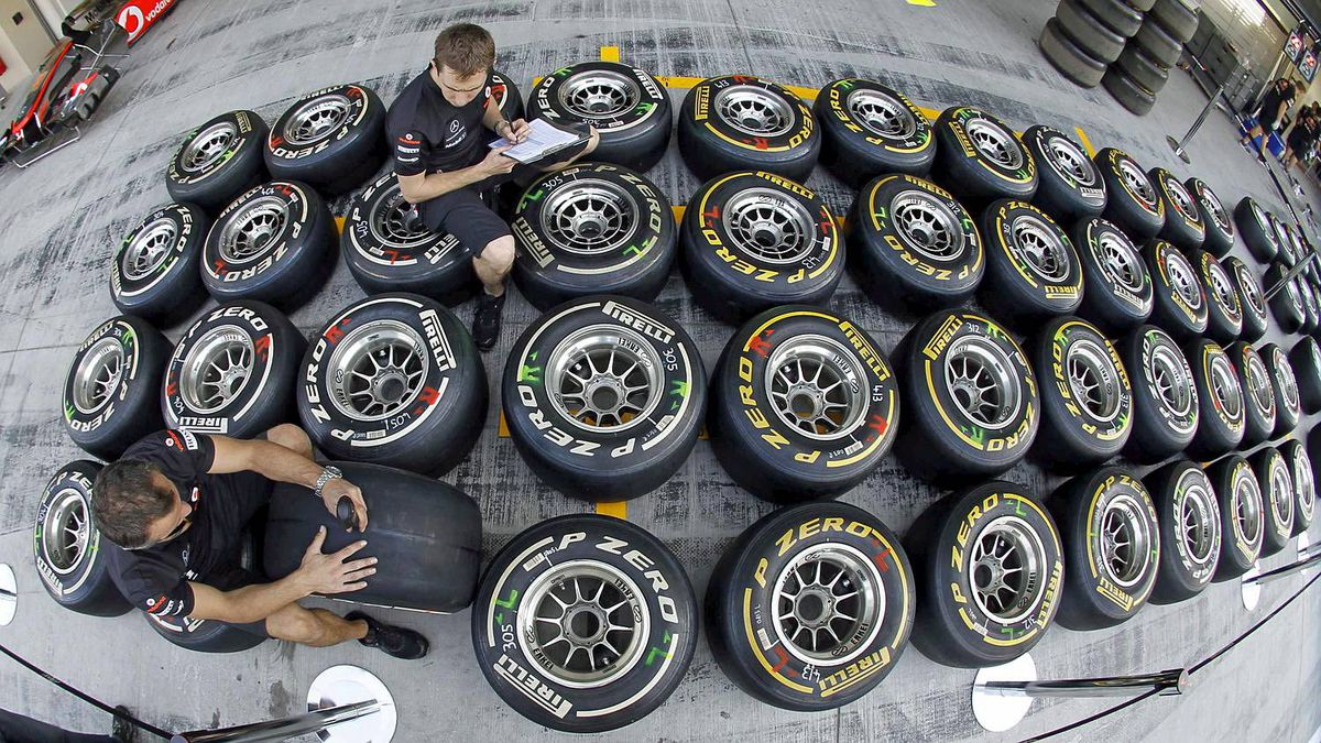 Red Bull technicans mark tires and take notes in the pit-lane ahead of the Abu Dhabi F1 Grand Prix at the Yas Marina circuit in Abu Dhabi