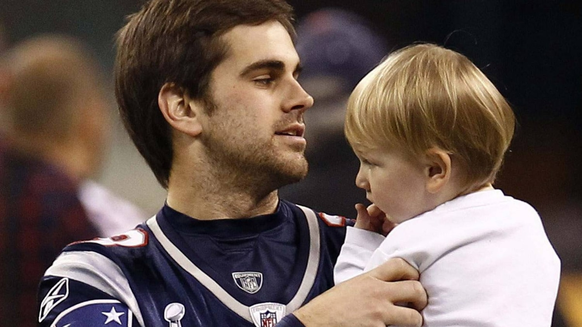 New England Patriots kicker Stephen Gostkowski holds his son Slayden as his wife Hallie looks on during a walk-through of the Lucas Oil Stadium before the Super Bowl XLVI NFL football game in Indianapolis, Indiana February 4, 2012. Super Bowl XLVI between the Patriots and the New York Giants is set for play on February 5. REUTERS/Jim Young