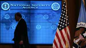 Former U.S. National Intelligence Director John Negroponte walks past a video screen at the National Security Agency at Fort Meade.