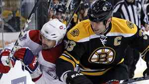Boston Bruins defenseman Zdeno Chara (33) checks Montreal Canadiens right wing Brian Gionta (21) against the boards as they chase the puck during the first period of an NHL hockey game in Boston, Wednesday, Feb. 9, 2011. (AP Photo/Elise Amendola)