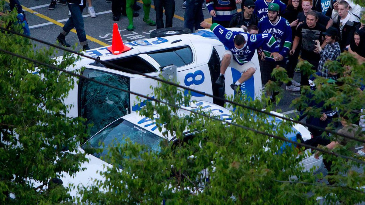 A man in a Canucks jersey jumps from an overturned police car onto another police vehicle during riots after the Canucks lost Game 7 of the NHL Stanley Cup Final to the Boston Bruins.