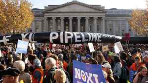 Demonstrators carry a giant mock pipeline while calling for the cancellation of the Keystone XL pipeline during a rally in Washington in this Nov. 6, 2011 file photo.