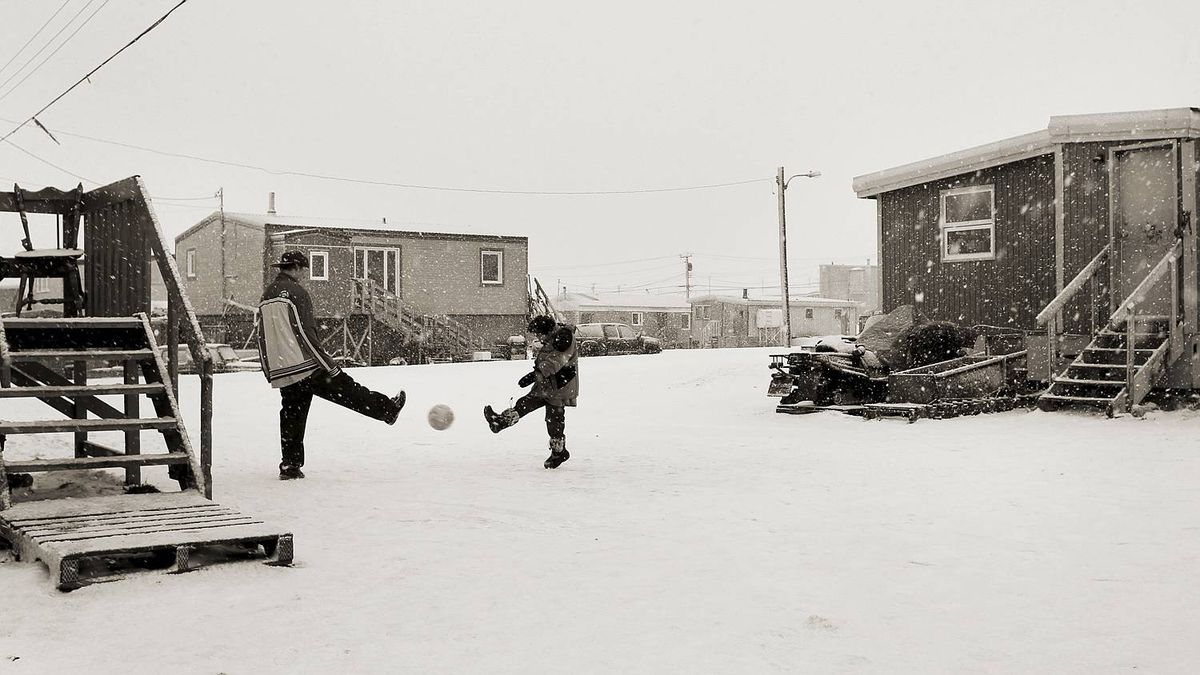 Two children play with a soccer ball in the snow in Iqaluit, Nunavut on November 12, 2010.