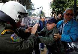 A pensioner pushes an anti-riot policeman during a protest against the government's new measures to freeze public sector pensions, in front of the prime minister's office in Athens March 3, 2010.