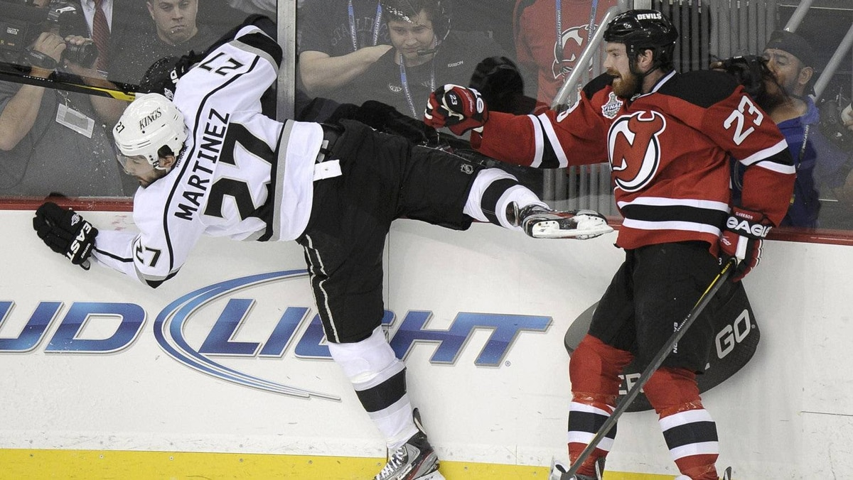 New Jersey Devils' David Clarkson (R) checks Los Angeles Kings' Alec Martinez during the first period in Game 1 of the NHL Stanley Cup final in Newark, New Jersey, May 30, 2012.