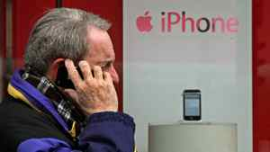 A man speaks on an iPhone as he walks past one on display in a Rogers Wireless retail store in Vancouver