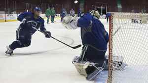Vancouver Canucks goaltender Roberto Luongo (R) blocks a shot from teammate Chris Higgins during a practice session in Vancouver, British Columbia, April 14, 2011. The Canucks will play the Chicago Blackhawks in game two of their NHL Western Conference quarter final April 15.