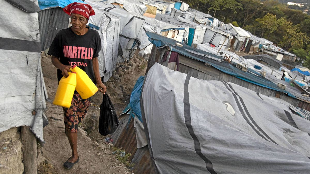 In this Jan. 5 photo, a woman wears a T-shirt with the name of President Michel Martelly as she walks through the Beaubin camp for people displaced by the 2010 earthquake in Petionville, Haiti.
